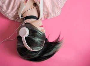 Mädchen mit Kopfhörern auf rosarotem Hintergrund